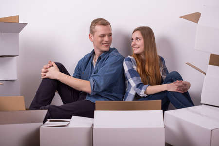 'young things': Image of young smiling pair sitting beside cardboard boxes