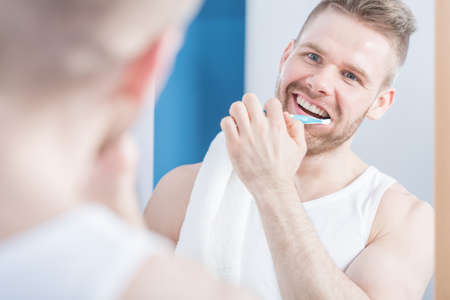 metrosexual: Attractive guy with perfect smile brushing his teeth