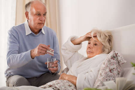 Elderly man giving his sick wife pills and a glass of water