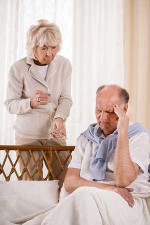 taking a wife: Man with migraine taking painkiller from his wife Stock Photo