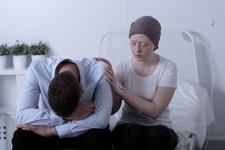 persona deprimida: Imagen de una niña con cáncer que consuela a su padre deprimido