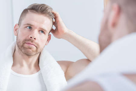 modelos masculinos: Chico guapo joven que mira en el espejo