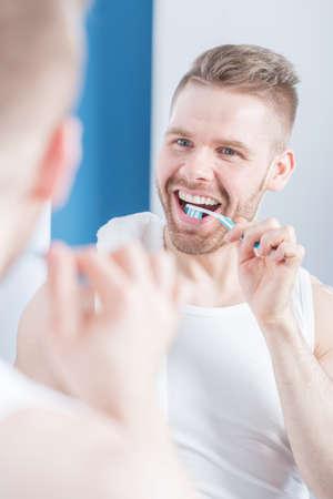 unshaved: Unshaved man brushing his teeth before meeting