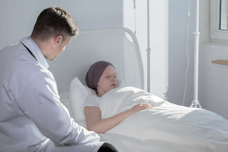 hospitalized: Photo of attentive medic and sleeping child with cancer Stock Photo