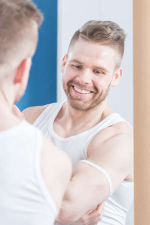modelos hombres: culturista atractiva que mide su bíceps después del entrenamiento Foto de archivo