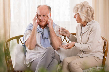 drink water: Wife helping husband with headache and giving him painkiller Stock Photo