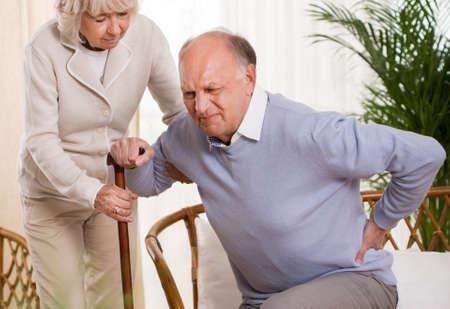 Frau hilft ein älterer Mann, der einen Rückenschmerzen mit