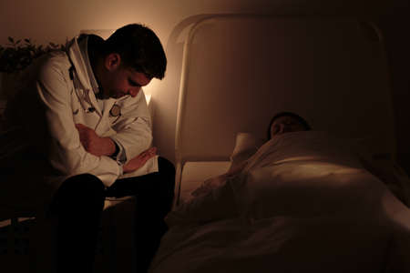 palliative: Doctor watching over his young patient with cancer