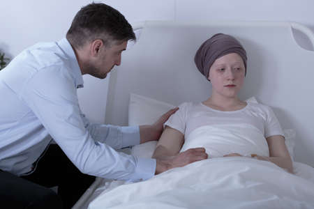 Picture of loving father supporting his sad daughter with cancer