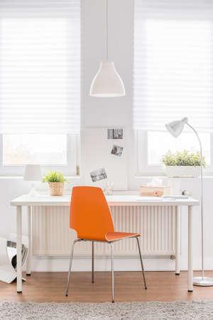 decoracion mesas: Imagen de escritorio blanco con la nueva silla de naranja Foto de archivo