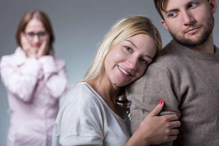 to interfere: Image of happy married couple and jealous mother-in-law Stock Photo