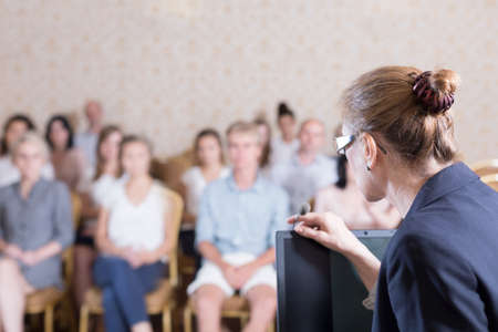 teach: Public speaker is speaking into the microphone Stock Photo