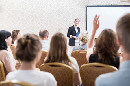 hall monitors: Woman is asking about something at the conference Stock Photo
