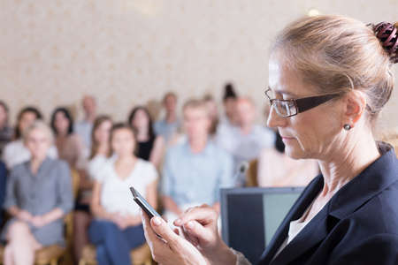hall monitors: Public speaker is texting during her conference Stock Photo