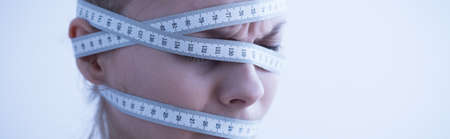 obsession: Female head wrapped in measuring tape - panorama