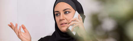 stereotypical: Panorama of irritared muslim woman talking on the phone Stock Photo