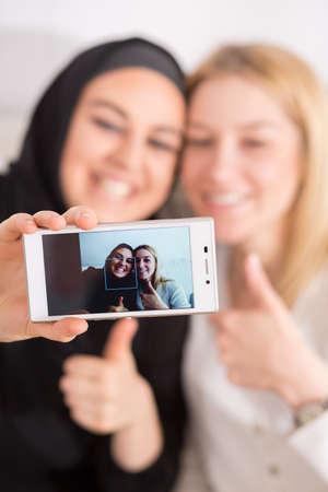 estereotipo: Sonre�r amigas musulmanes y europeos que toman selfie