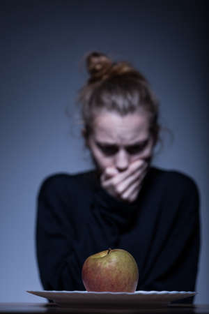 refusing: Young anorexic woman refusing to eat an apple