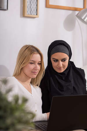 Young smiling female friends looking in laptop