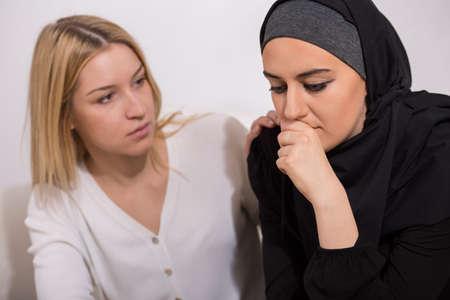 pretty blonde girl: Worried arab woman with her european friend