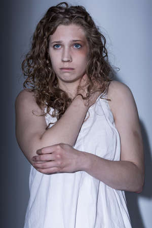 raped: Female victim in underwear covering herself up Stock Photo