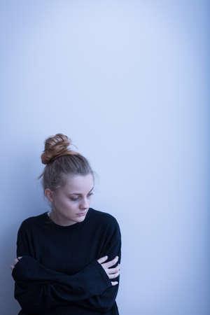 Mujer joven con la depresión en el fondo gris Foto de archivo - 48557514