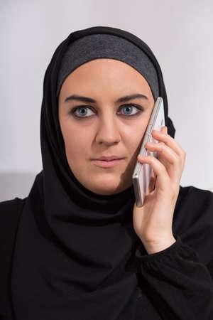 estereotipo: Foto de cabeza de la chica joven �rabe que habla en el tel�fono