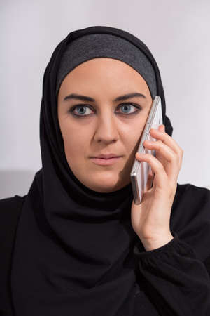 Headshot of young arab girl talking on the phone Foto de archivo