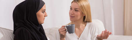 tolerance: Woman discussing with a muslim friend in her house Stock Photo