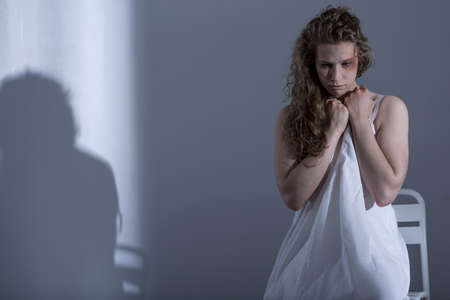 battered woman: Young assaulted woman sitting in underwear in dark room Stock Photo