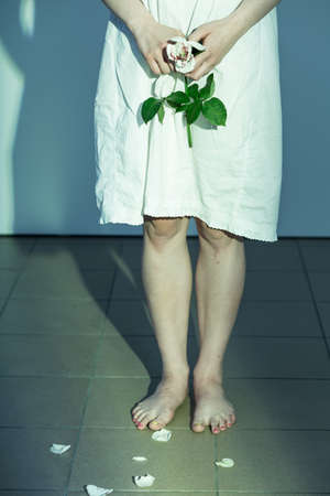 raped: Girl holding a white rose with blood on its petals Stock Photo