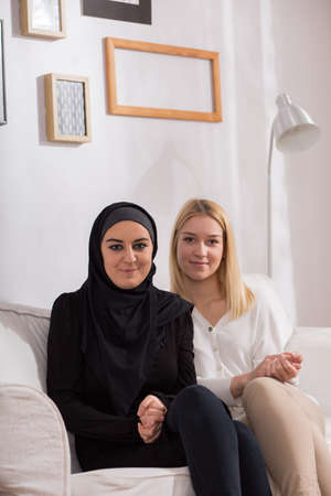 blond girl: Muslim girl in hijab and her european friend Stock Photo