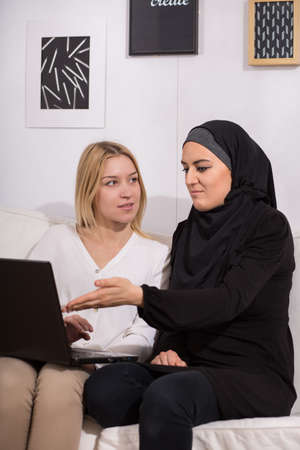 Muslim woman talking to a friend with a laptop