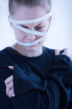 thinness: Young anorexic woman wrapped in tape measure Stock Photo