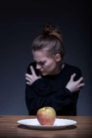Young woman with anorexia refusing to eat an apple