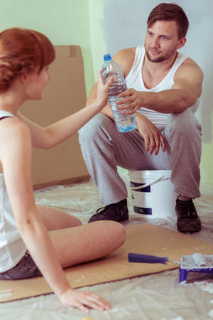 redecoration: Young couple is resting after painting walls Stock Photo