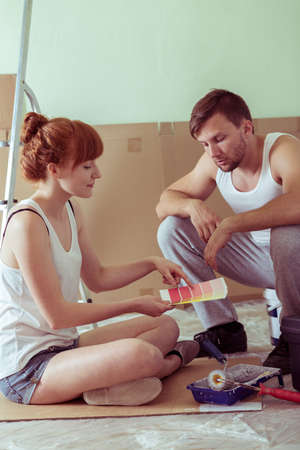 Young couple is choosing new color of the walls
