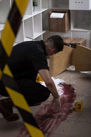 fingerprinting: Police officer is investigating at the crime scene Stock Photo