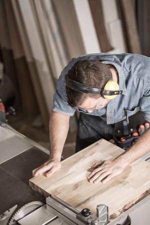 skill: Photo of professional carpenter in muffs cutting board