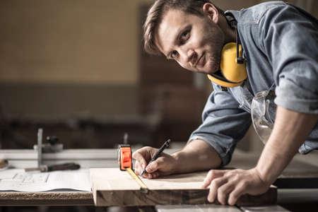 caja fuerte: Foto de guapo carpintero medir tabla de madera Foto de archivo