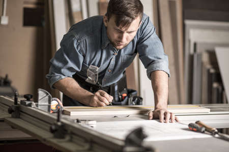 ハンサムな木工家で取り組んでいるプロの固体ワークベンチの画像