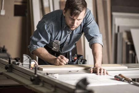 Beeld van de knappe houtbewerker werken aan professionele solide werkbank Stockfoto