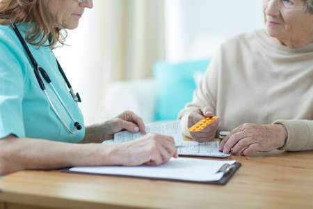 medicament: Female doctor prescribing medicament for senior woman