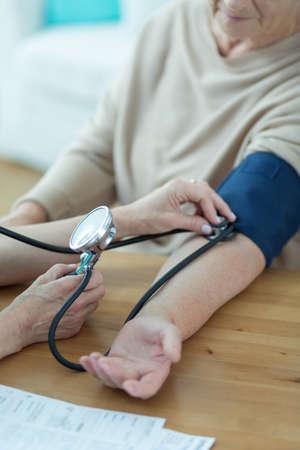 hipertension: Una más vieja mujer que tiene la presión arterial medida por el cardiólogo