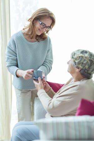 ayudando: Cuidador Mujer ayuda a la mujer mayor en su casa