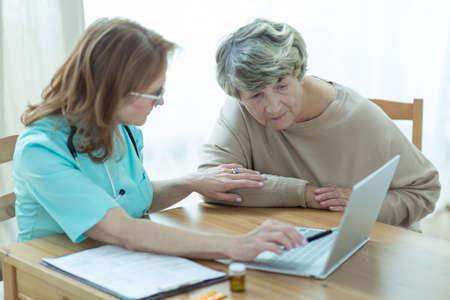 uniformes de oficina: Médico y el paciente mirando la pantalla del ordenador portátil Foto de archivo