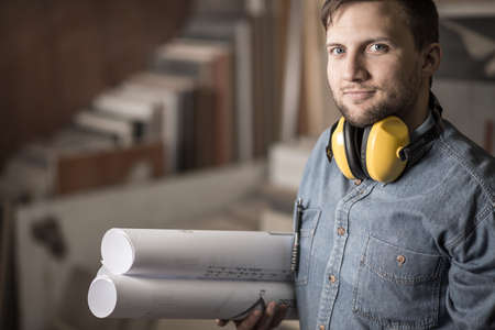 Portrait of young accurate joiner with muffs holding projects