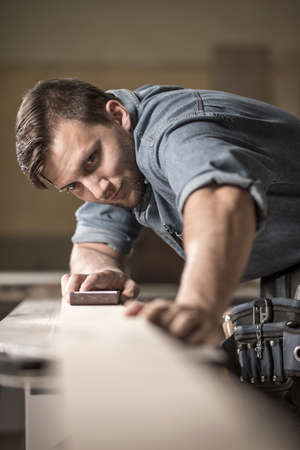 joiner: Image of young skilled joiner polishing wooden board