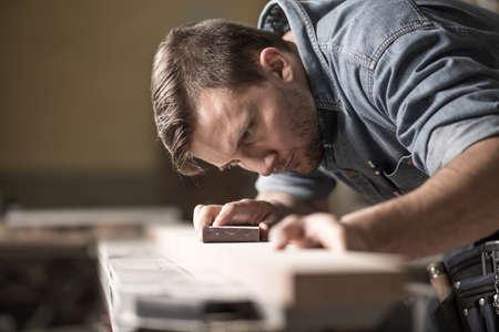 Portrait of handsome precise cabinetmaker during work in workshop