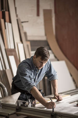 彼のワーク ショップでの精度で熟練した大工の写真